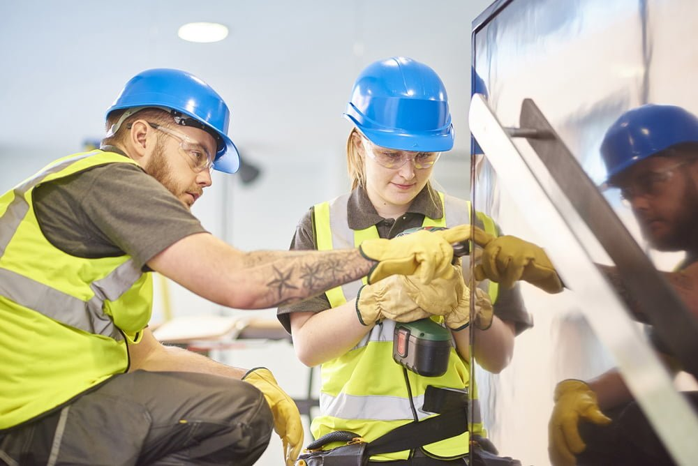 Two employees following a safety guideline to make sure job is done correctly